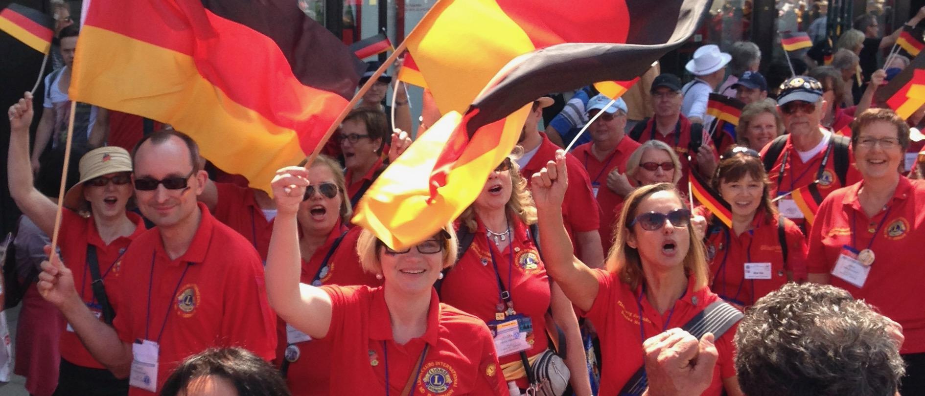 Fahnen schwenkende Lionsmitglieder bei der Internationalen Parade einer Lions-Convention.