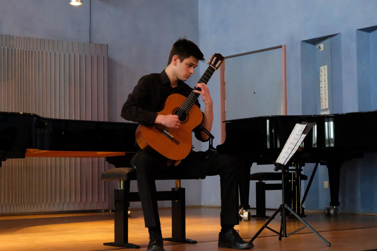 Ein junger Mann spielt beim Wettbewerb Klassische Gitarre