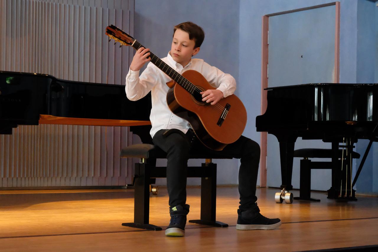 Ein anderer junger Mann spielt beim Wettbewerb Klassische Gitarre