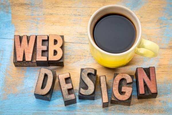 Webdesign Symbolbild - Schriftzug Webdesign und ein Becher Kaffee